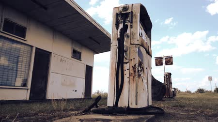 petrol : Rusted on pump put the front of an abandoned fuel station.