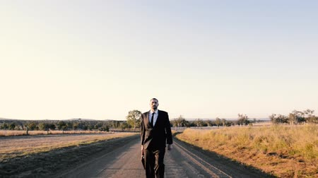 özgürlük : Concept: A frustrated business man is leaving the corporate lifestyle and chasing freedom in the outback of Queensland, Australia. Cinematic Portrait Style. Stok Video