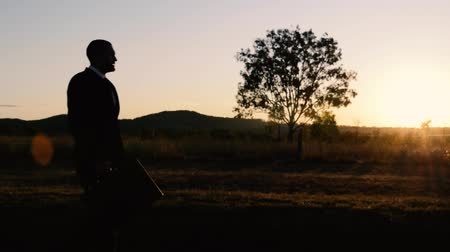 путешествие : Concept: A frustrated business man is leaving the corporate lifestyle and chasing freedom in the outback of Queensland, Australia. Cinematic Portrait Style. Стоковые видеозаписи