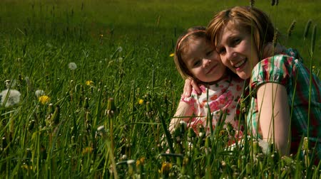 csókolózás : Mother and daughter are cuddling in the evening light on a meadow Stock mozgókép