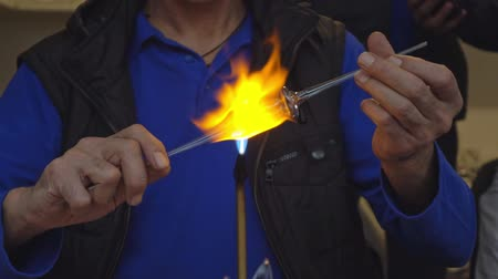gas burner flame : hands master heat up the glass rod.