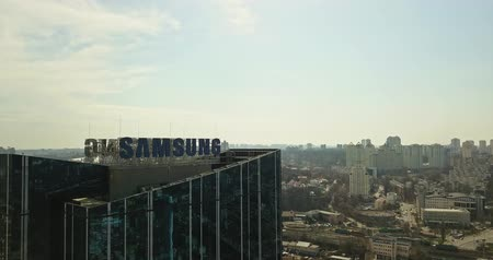 convenção : Kiev, Ukraine - April 7, 2018: Samsung sign on a Samsung glass building, skyscraper headquarters of the famous phone brand in the city of Kiev