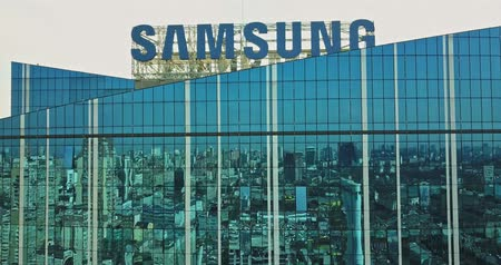 Kiev, Ukraine - April 7, 2018: cityscape reflection on a glass Samsung facade building and Samsung sign with aerial view buildings city and railway station in Kiev Stok Video