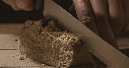 cereal product : A man cuts a soft bread with a bread knife on a wooden board
