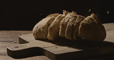 elválasztott : Sliced fresh bread falls on a wooden board on a dark background