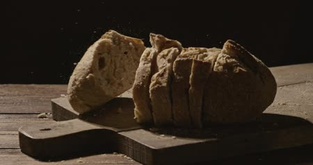 elválasztott : sliced fresh homemade bread falls on a wooden board on a dark background Stock mozgókép