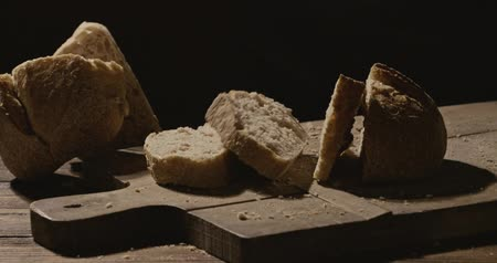 potraviny : Homemade organic bread falls on a wooden board on a dark background