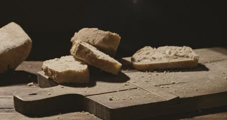 elválasztott : Pieces of freshly baked bread fall on a wooden board and table on a dark background Stock mozgókép