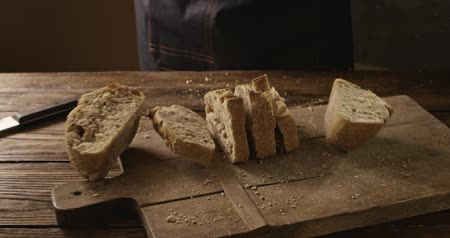 begging : A fresh soft sliced bread baker throws on a chopping wooden board Stock Footage