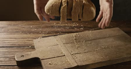 begging : A man throws sliced fresh bread on an old wooden cutting board
