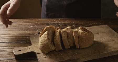 Pieces of fresh homemade bread a man throws on a wooden board Stok Video