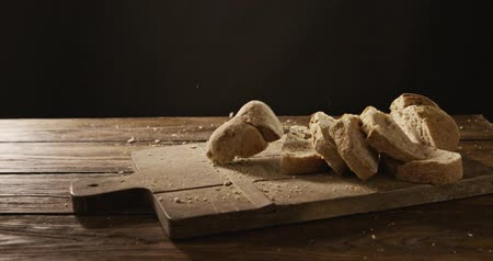 Freshly baked sliced bread falls on a wooden board against the background of an old wooden table