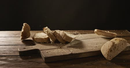 Pieces of bread fall on a wooden board and crumble Stok Video