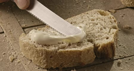fatty acid : A man is spreading a knife on a piece of bread, a soft pate cheese