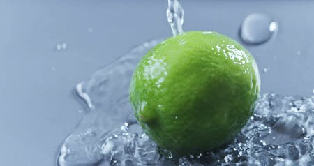 calcário : A stream of water pours on the green lime on a gray glass background. Slow motion 2k video shooted on 240 fps Stock Footage