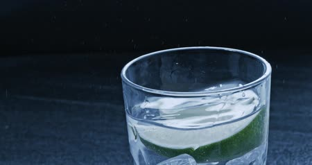 tonik : A piece of lime falls into a glass with water and ice. Slow motion 2k video shooted on 240 fps