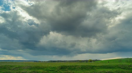 morning : Rain clouds at wild field at spring. Time lapse.