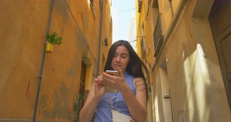 Young woman walking in city at morning and using smartphone. Girl browse the Internet, texting with someone. Wideo