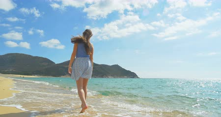 Attractive Female walking along sandy Beach. Clear blue water Wideo