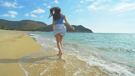 Attractive Female Running along sandy Beach. Clear blue water Slow Motion