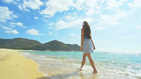 Attractive Female walking along sandy Beach. Clear blue water Slow Motion