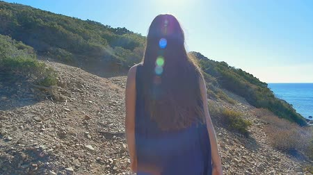 Pretty young woman tourist walking in the desert mountains near sea. Slow motion.