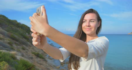 Young pretty woman doing selfie photo using her smartphone over sea. Female standing near the sea during sunset. Clear blue water.
