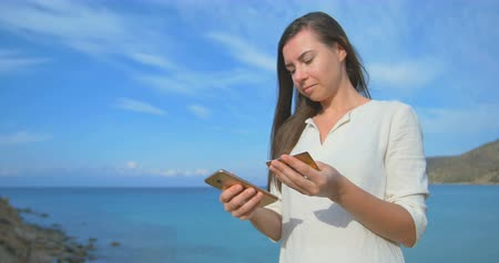 Woman using credit card on vacation shopping online with mobile phone at clear blue sea background