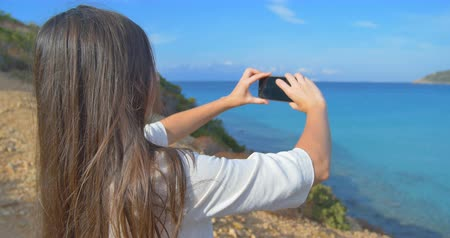 photograph : Attractive women making photos of sea with smartphone. Hills and clear blue water.