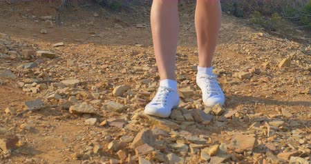 Beautiful woman legs in white sneakers, going along the stony ground. Walking in the desert.