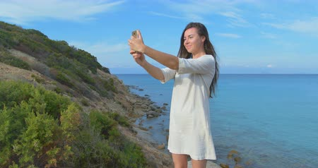 self portrait photography : Young pretty woman doing selfie photo using her smartphone over sea. Female standing near the sea during sunset. Clear blue water.