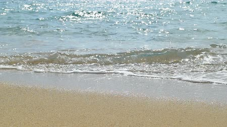 Waves landing on sandy beach. Clear blue water. Slow motion. Wideo