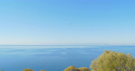 The helicopter is flying over the sea. Panoramic view at summer sunny day. Sea landscape.