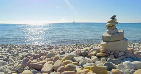 Waves landing on stone beach. Meditation, stone pyramide. Clear blue water.