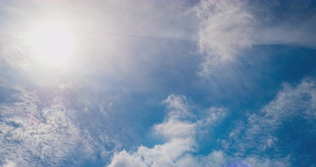 lightweight : White clouds flying on blue sky with sun rays. Sun beams. Time lapse.