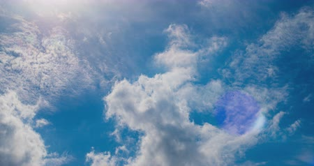 radiante : White clouds flying on blue sky with sun rays. Sun beams. Time lapse.