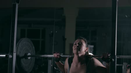 A woman crouches with a heavy barbell on her shoulders Vídeos