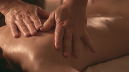 The masseur kneads the back of the girl Vídeos