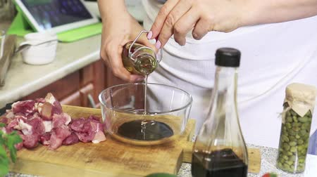 cooking pots : Woman preparing a marinade for meat chopped fresh pork in the kitchen. Balsamic vinegar, oil and pepper chilli, svanska salt, spices, herbs, wooden board, glass bowl. Stock Footage