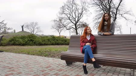 Female teenagers listening to music on smartphone at the bench in an autumn city park Vídeos
