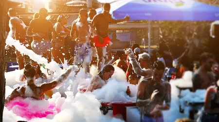 Budva, Montenegro, 15th august 2017: Boys and girls are bathing and dancing in foam on the foam party, Slow Motion Video clip