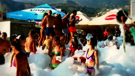 Budva, Montenegro, 15th august 2017: Boys and girls are bathing and dancing in foam on the foam party, 4 K Video clip