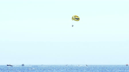 Budva, Montenegro, 15th August 2017: Tourists at the sea fly with the big yellow parachute, 4 K Video Clip