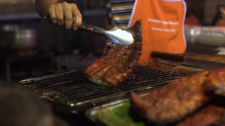 ped : Street food: Thai man fries pork ribs at the night food market in Pattaya, Thailand