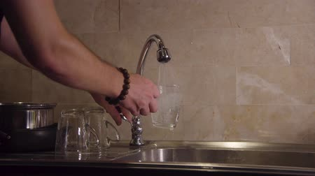 doldurmak : 4K pours water from the tap into a clear glass Stok Video