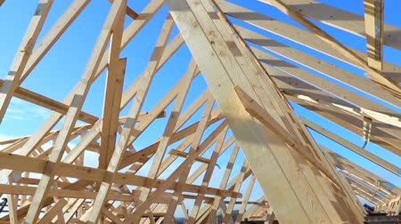 лесоматериалы : New residential construction home framing against a blue sky