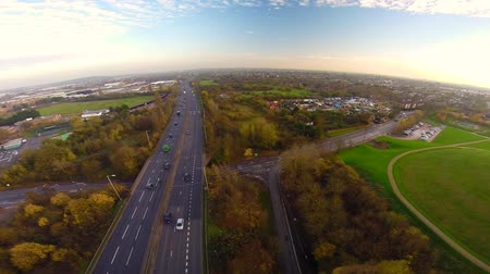 otoyol : Aerial view of a truck and other traffic driving along a road on the outskirts of a city in the UK Stok Video
