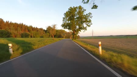 previously : Car driving in evening spring countryside on a sunny day. Landscape with trees and blue sky with sunlight, travel and transportation concepts. 60 FPS POV view