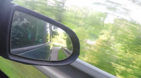 previously : Mirror back view from the car in the spring landscape Landscape with trees and sunlight Stock Footage