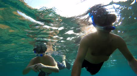 action animals : Underwater shot of a young boy snorkelling and diving with a father in a tropical sea in Nusa penida, Indonesia, Bali